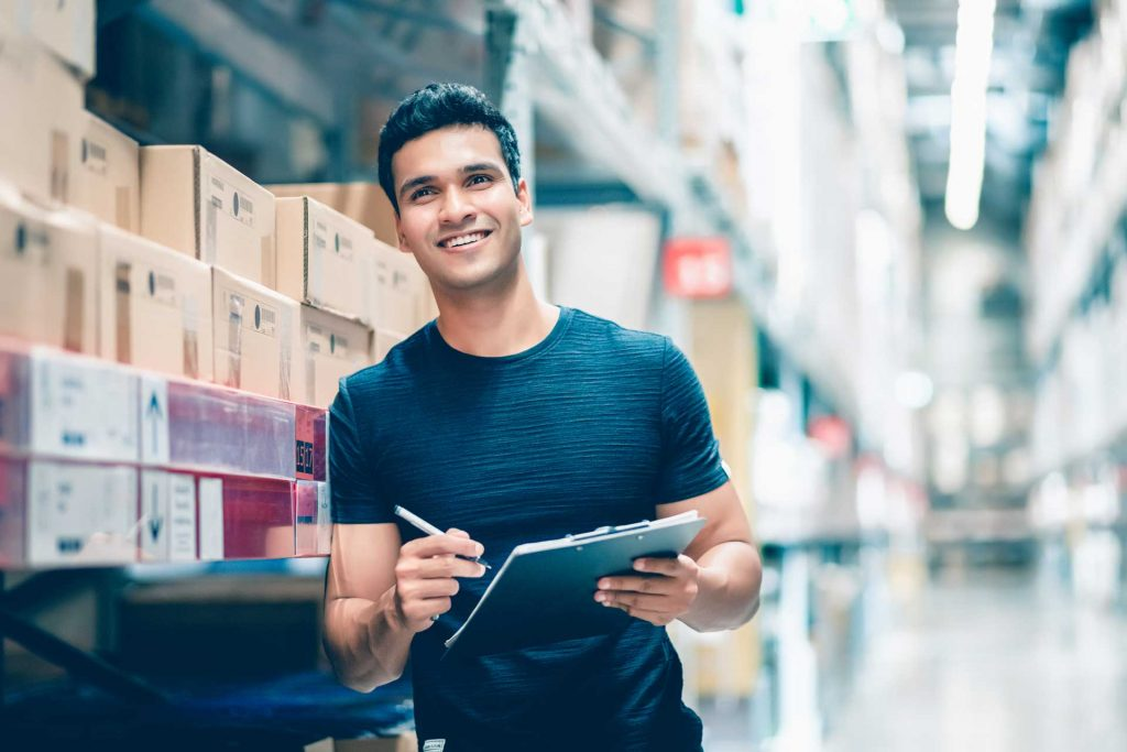 man in warehouse signing off packages